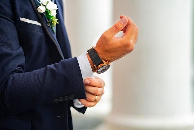 Der mann in einem klassischen blauen anzug passt den manschettenknopf an der hemdmanschette zum valentinstag oder zur hochzeit an