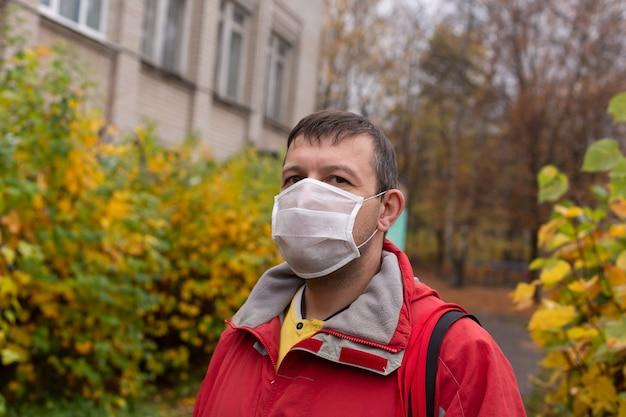 Der mann in einer schutzmaske auf der straße, herbst