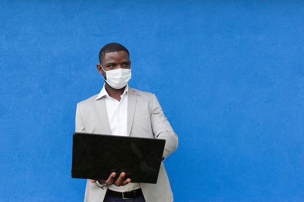 Der mann in einer schutzmaske mit einem laptop in der hand
