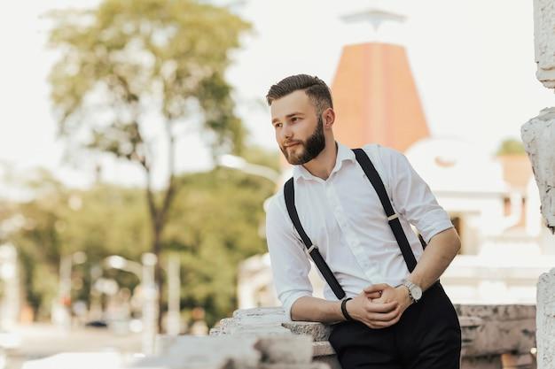Der mann in klassischer kleidung steht auf dem balkon und schaut weg.