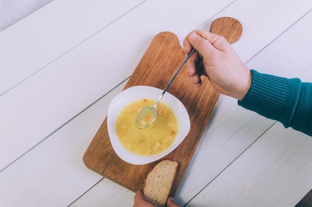 Der mann isst brühe suppe aus einer schüssel.