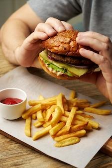 Der mann isst einen burger, nahaufnahme. junger mann mit hamburger, pommes frites und sodagetränk. kerl am fast-food-restauranttisch