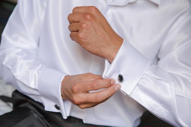 Der mann knöpft sein hemd zu. morgen des bräutigams. hände des hochzeitsbräutigams knöpfen das weiße hemd zu.