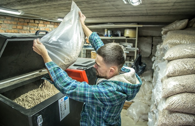 Der mann lädt die pellets in den festbrennstoffkessel, arbeitet mit biokraftstoffen und spart wirtschaftlich