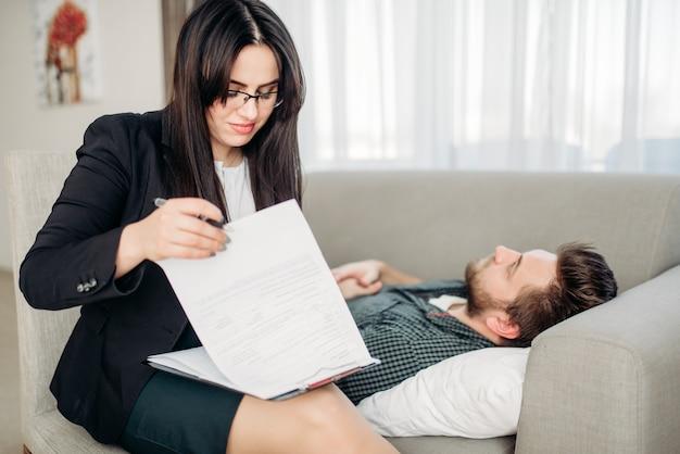 Der mann liegt auf dem sofa beim empfang eines psychotherapeuten