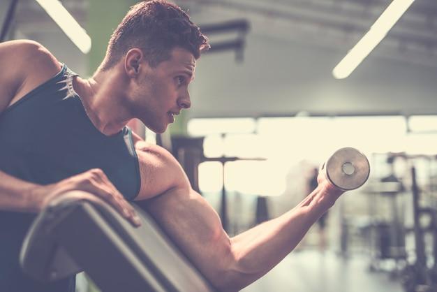 Der mann macht bizepsübungen mit einer hantel im fitnessstudio