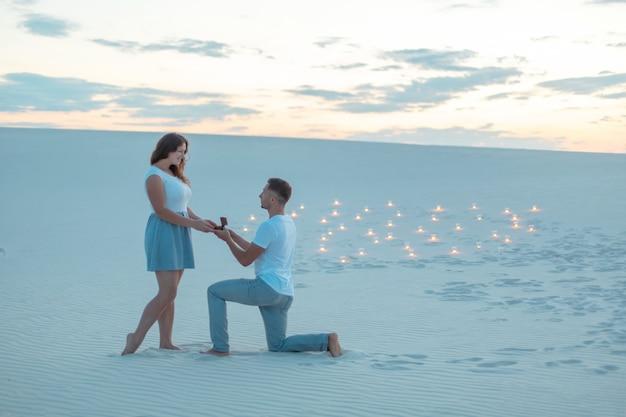 Der mann macht dem mädchen einen heiratsantrag, indem er sein knie biegt, während er in der wüste im sand steht. abends brennen kerzen im sand