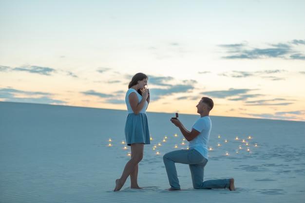 Der mann macht dem mädchen einen heiratsantrag, indem er sein knie biegt, während er in der wüste im sand steht.