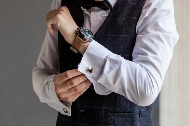 Der mann macht sich bereit für die arbeit, indem er sein businesshemd zuknöpft. morgenvorbereitung des bräutigams vor der hochzeit