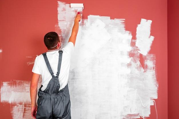 Der mann malt die wände und die decke in weißer farbe. bemalung und reparatur des raumes.