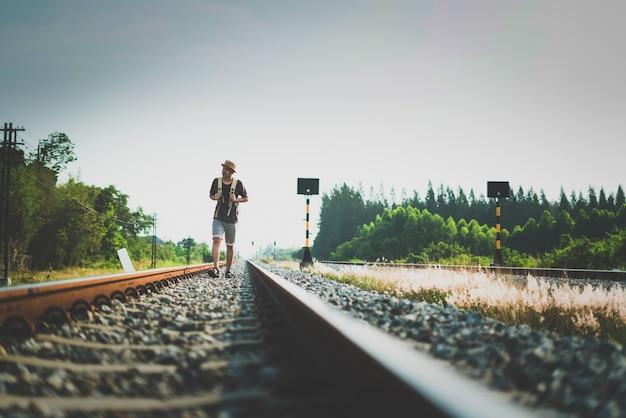 Der mann mit dem rucksack gehend weg auf eisenbahn und betonen zur geduld und zum übersichtsversuch schritt vorwärts zum ziel.