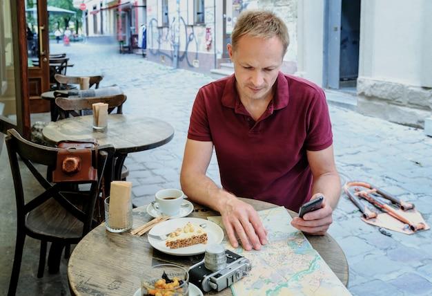 Der mann mit dem smartphone sitzt am kaffeetisch auf der straße.