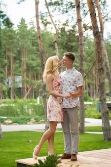 Der mann mit der frau schaut sich mit liebe an. ein romantisches date in einem pinienwald, liebespaar eines schönen paares
