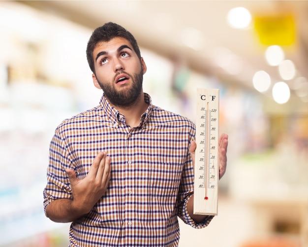 Der mann mit einem großen thermometer in einer hand