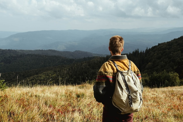 Der mann mit einem rucksack auf dem gipfel eines berges