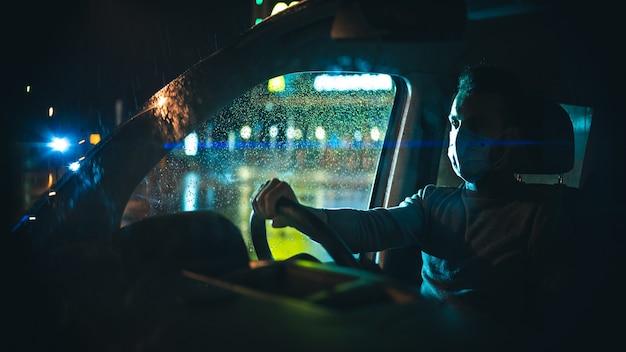 Der mann mit medizinischer maske, der das auto auf der nächtlichen regnerischen straße fährt