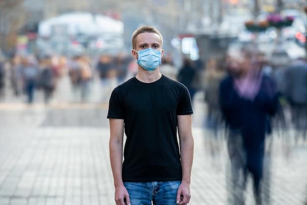 Der mann mit medizinischer maske im gesicht steht mitten im menschenstrom