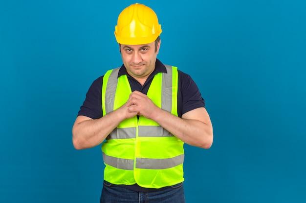 Der mann mittleren alters des konstrukteurs, der die gelbe weste der konstruktion und den schutzhelm hält, die hände zusammenhalten, die etwas planen, haben interessante idee über isolierter blauer wand