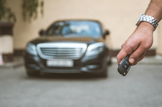 Der mann öffnet das auto mit einem schlüsselbund, im hintergrund ein schwarzes auto.