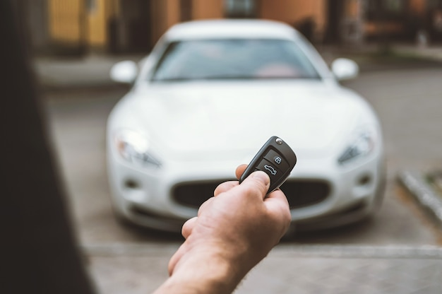 Der mann öffnet das auto mit einem schlüsselbund, im hintergrund ein weißes auto.