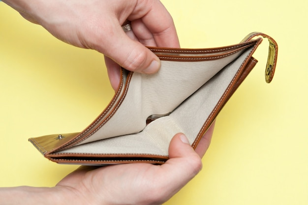 Der mann öffnet eine leere geldbörse ohne geld. nahansicht.