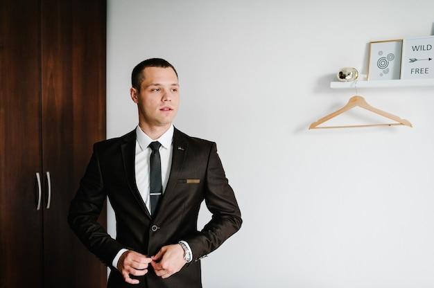 Der mann passt zu hause eine jacke an. nahansicht. hübsches mannmodell im formellen anzug, hemd, krawatte steht im raum. kleidungskonzept. der bräutigam am hochzeitsmorgen.