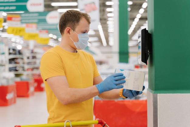 Der mann posiert im großen einkaufszentrum, scannt den preis von etwas in der schachtel und macht einen kauf