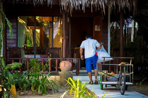 Der mann räumt auf. tropisches bungalowhotel. es gibt einen reinigungsservice. der reiniger funktioniert.