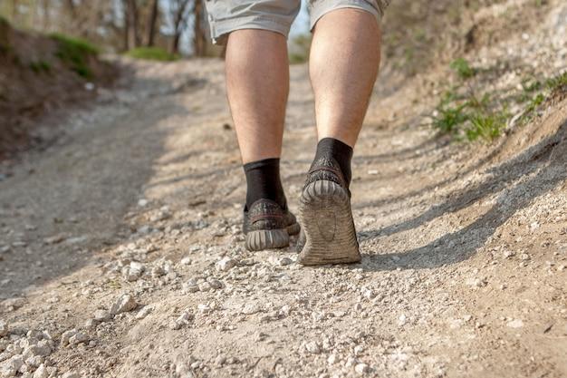 Der mann rennt den weg entlang. smart laufen durch den wald. konzept von training, leichtathletik, hindernisrennen, sportwandern