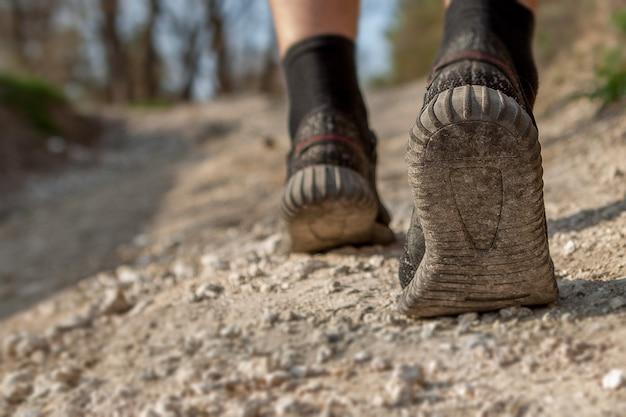 Der mann rennt den weg entlang. smart laufen durch den wald. konzept von training, leichtathletik, hindernisrennen, sportwandern.