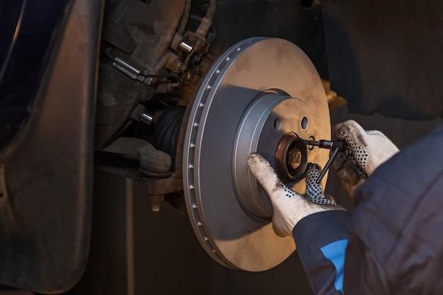 Der mann repariert die scheibenbremse im auto. scheibenbremse reparieren.
