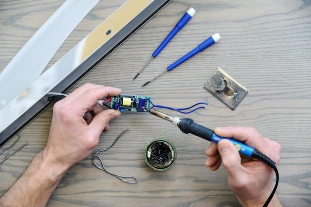 Der mann repariert die stromversorgung der lampe. er hält eine elektronische platine und einen lötkolben in der hand. draufsicht.