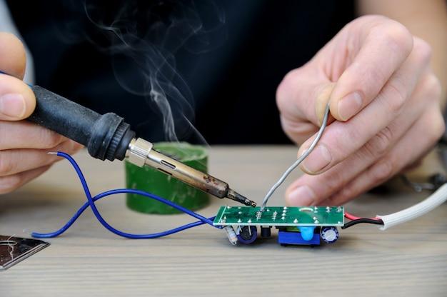 Der mann repariert die stromversorgung der lampe. er hält eine elektronische platine und einen lötkolben in der hand.