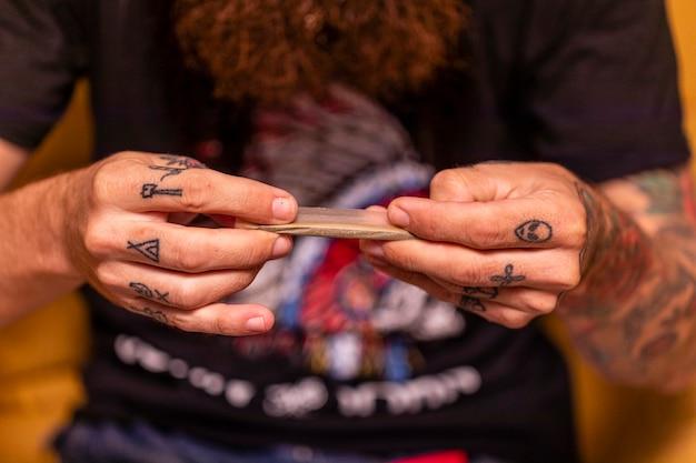 Der mann rollte den joint aus frischem marihuana-unkraut.