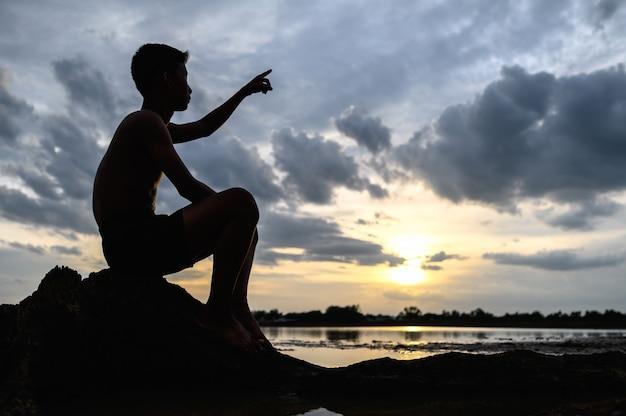 Der mann saß auf der basis des baumes und zeigte mit den händen nach vorne während des sonnenuntergangs.