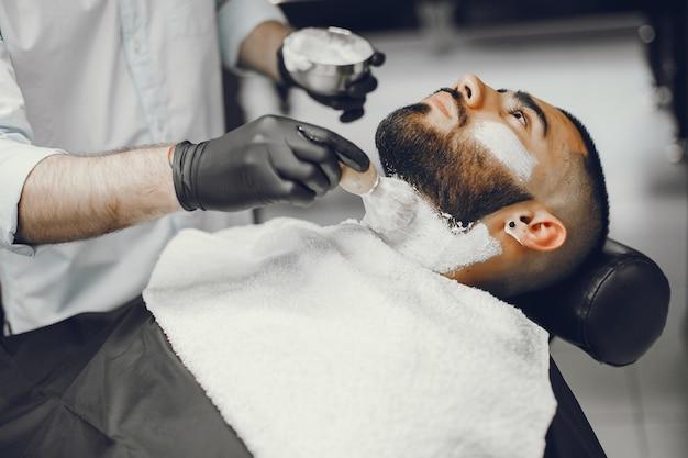 Der mann schneidet seinen bart in den friseursalon.