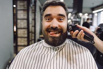 Der Mann sieht lustig aus, während der Barbier im Friseursalon an ihm arbeitet