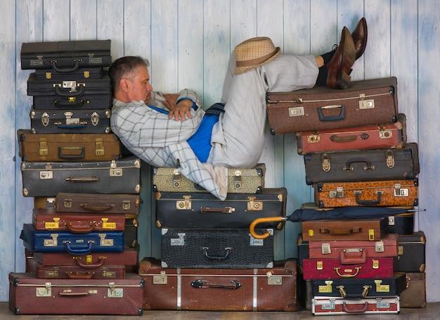 Der mann sitzt auf alten koffern