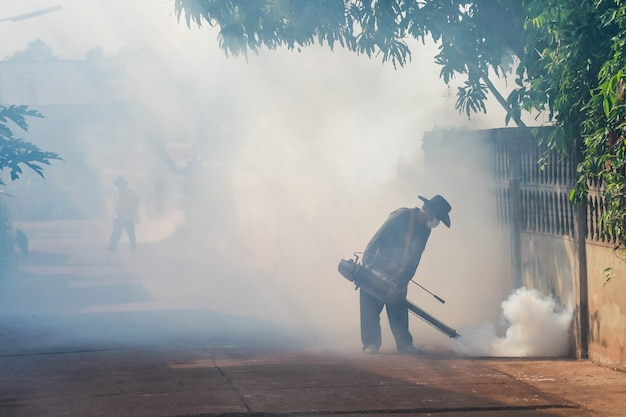 Der mann sprüht dämpfe im dorf, um dengue-fieber zu verhindern.