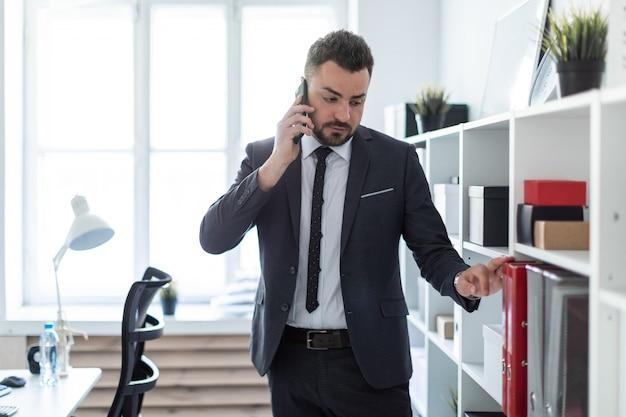 Der mann steht in der nähe der regale im büro, telefoniert und legt seine hand auf die mappe.