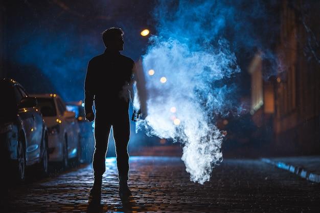 Der mann steht in der nähe des rauchs. abend nachtzeit. aufnahme mit teleobjektiv