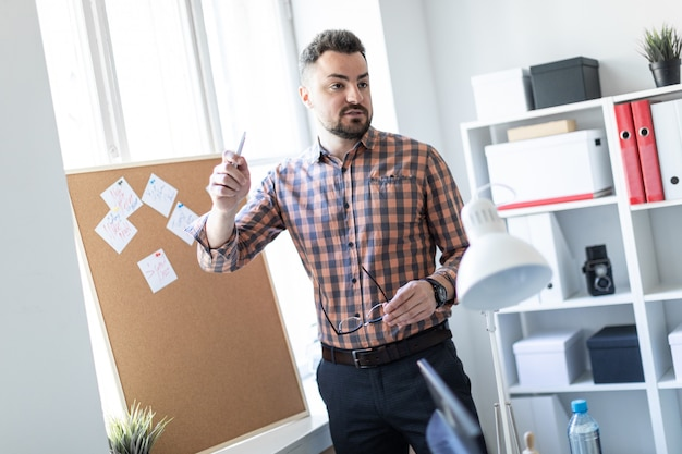 Der mann steht mit aufklebern im büro neben der tafel und führt eine besside.