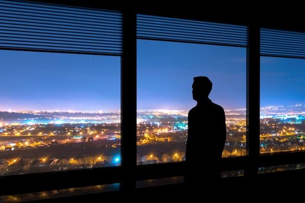 Der mann steht neben dem fenster auf dem stadtbildhintergrund
