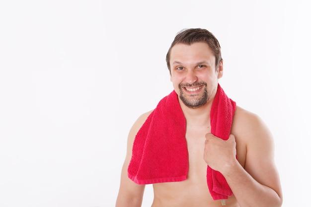 Der mann streichelt seinen bart. morgenbehandlungen im badezimmer. blaues handtuch um ihren hals. isoliert auf einem weißen hintergrund. speicherplatz kopieren