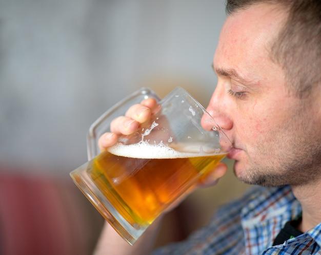 Der mann trinkt ein frisches, kaltes alkoholisches bier aus einem großen becher