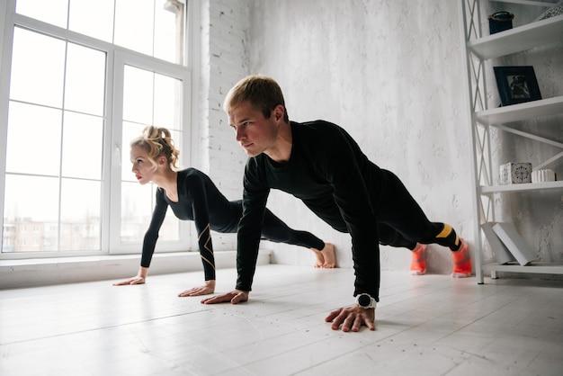 Der mann und das mädchen im trainingsanzug. schwarze sportuniform. männliche und weibliche athleten. aufgepumpter körper. liegestütze. morgentliches training. reihe von übungen für den körper. klassen zu zweit. zu hause zusammen trainieren.