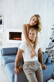 Der mann und das mädchen umarmen und küssen sich auf der blauen couch. weihnachtsbaum geschmückt. elektronischer kamin. blond in einem weißen t-shirt und jeans.