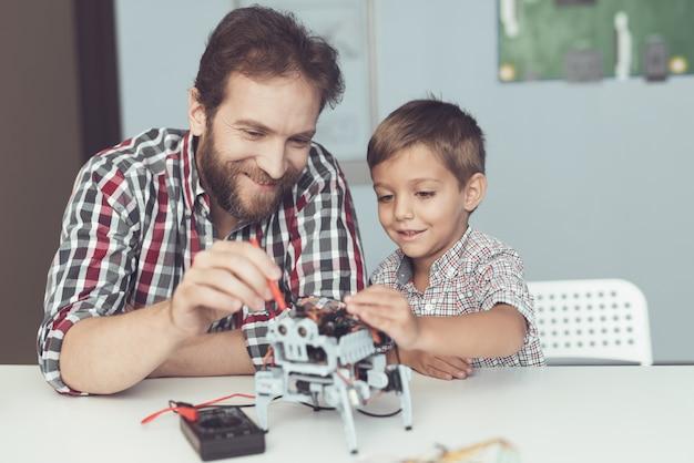 Der mann und der kleine junge messen die leistung des roboters.