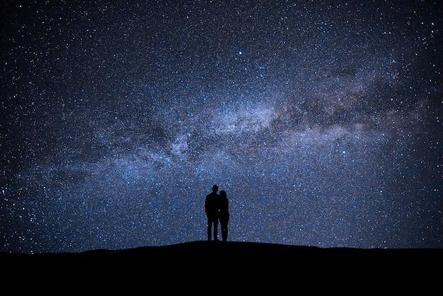 Der mann und die frau, die am himmel mit sternenhintergrund stehen