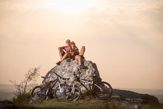 Der mann und die frau, die auf einem stein nahe ihnen sitzen, tragen fahrräder zur schau